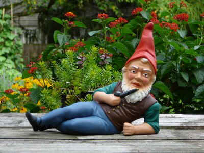 Gnome brazenly lounging about a deck at a human home with magical minty clove pipe in hand.
